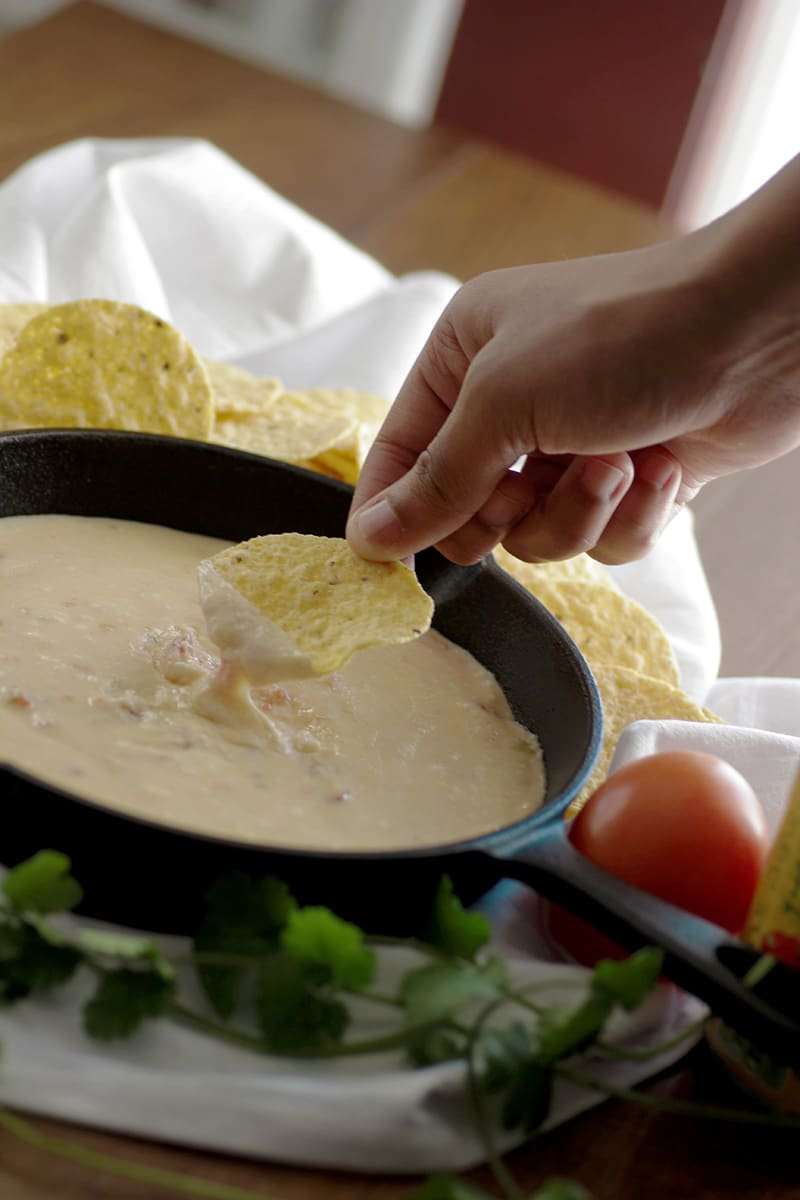 person dipping tortilla chip in creamy white queso dip in cast iron skillet