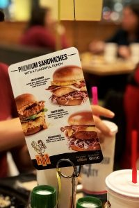 PDQ chicken sandwiches listed on table placard