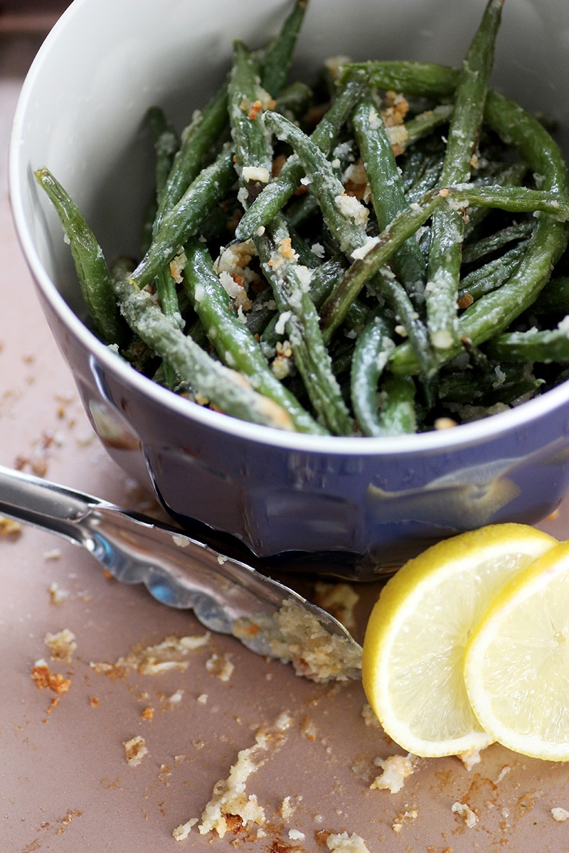 green beans in blue bowl sitting on pink pan with lemons
