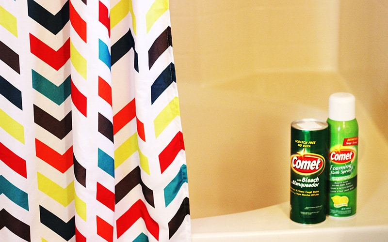 comet powder and comet foaming bath spray on tub ledge with multi color shower curtain