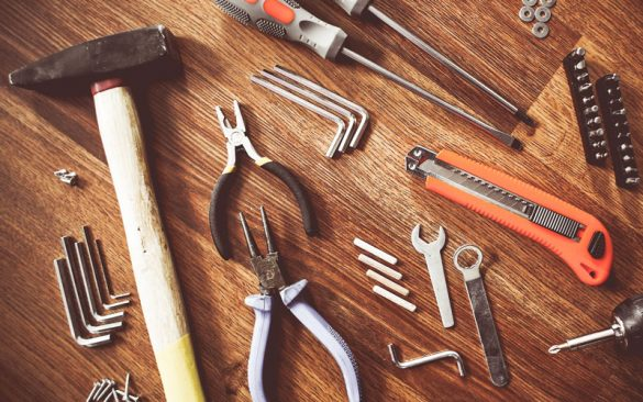 pliers, hammer, drill bits, wrench on wooden table