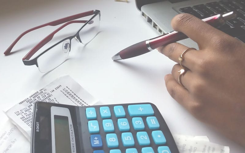 Am I a Homemaker | woman with pen and calculator paying bills