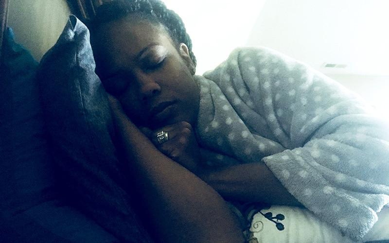 black woman sleeping in gray polka dot rob