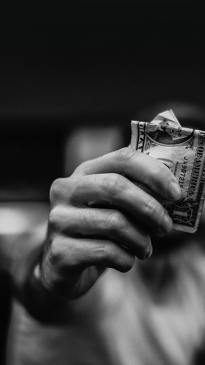 hand holding out one dollar bill in cash to negotiate a fair price