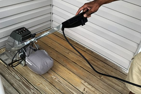 sanding porch using sander before applying waterproofing stain