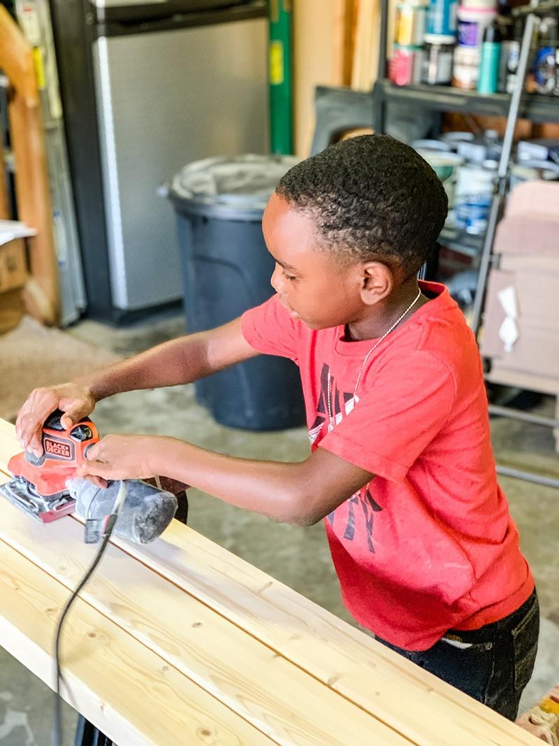 little boy sanding shelf