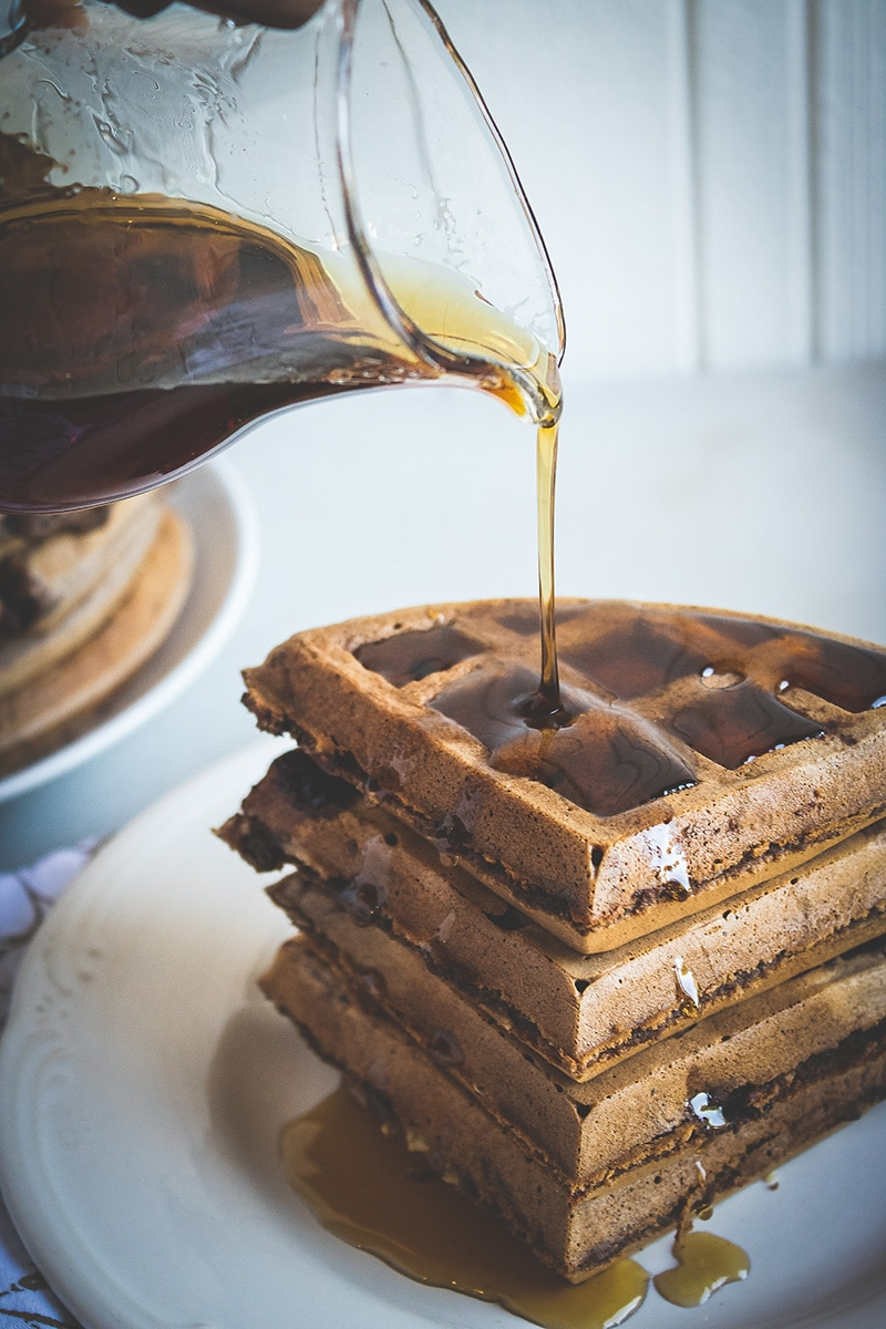 syrup being poured over stack of double chocolate banana waffles