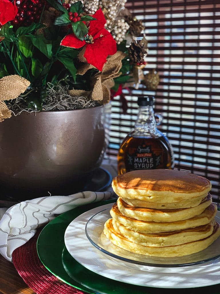 fluffy eggnog pancakes on plate with maple syrup