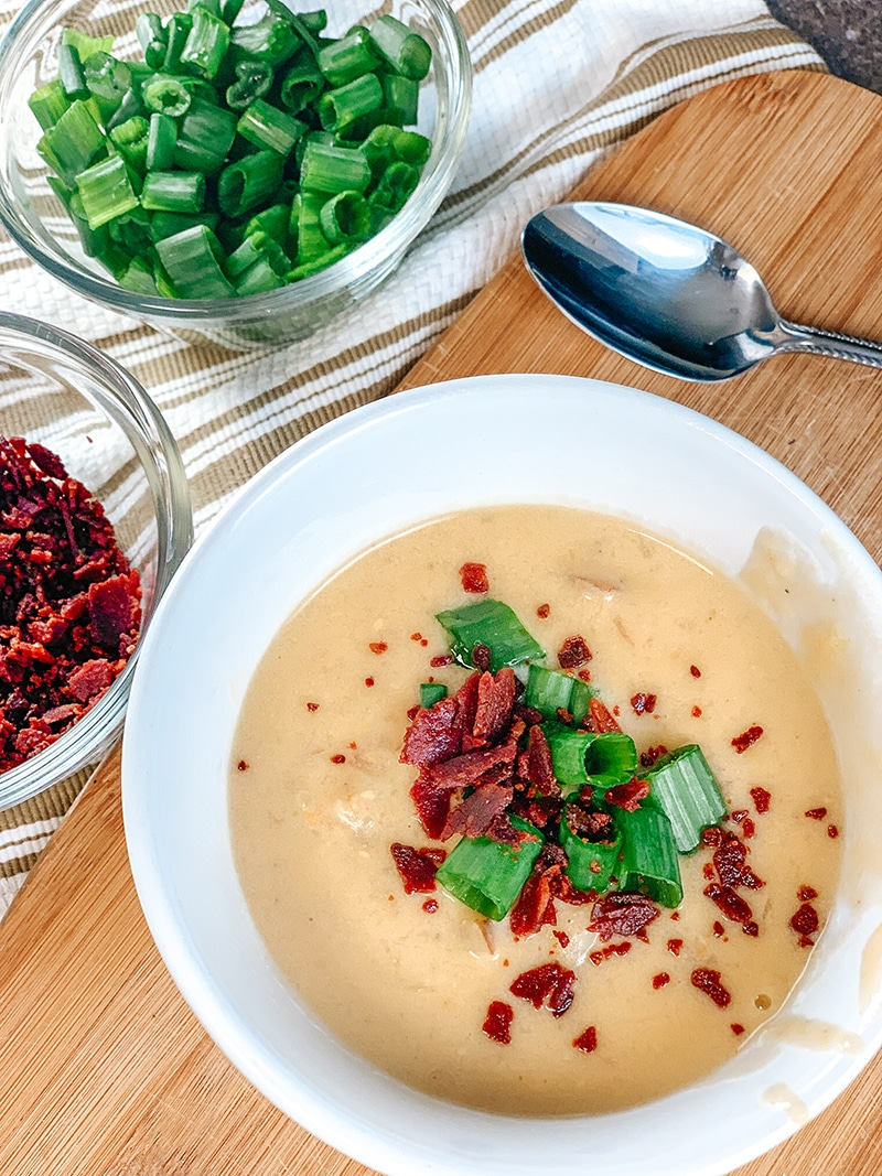 instant pot baked potato soup topped with bacon pieces and green onions