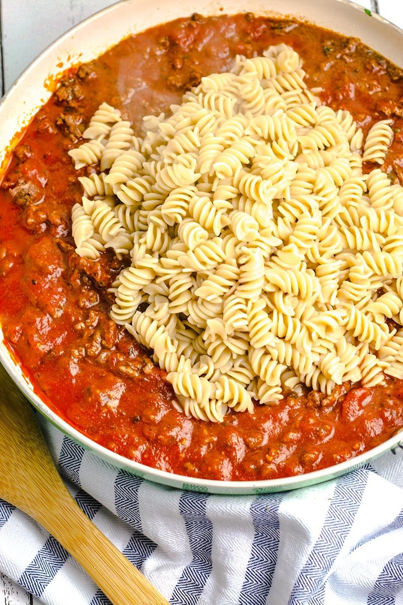 mixing pasta and sauce